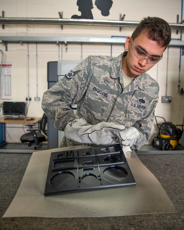 U.S. Air Force Staff Sgt. Montana Engelking, 100th Maintenance Squadron aircraft metals technology welder machinist, removes foundation material from a 3D print mold at RAF Mildenhall, England, Aug. 23, 2018. The shop creates parts that can't be individually purchased, such as grease caps for equipment. (U.S. Air Force photo by Senior Airman Christine Groening)