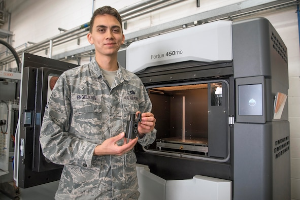 U.S. Air Force Staff Sgt. Montana Engelking, 100th Maintenance Squadron aircraft metals technology welder machinist, holds a 3D printer example at RAF Mildenhall, England, Aug. 23, 2018. The printer can print anything from 14 inches in length, 14 inches wide and 16 inches tall and as thin as 10 thousandths of an inch. (U.S. Air Force photo by Senior Airman Christine Groening)