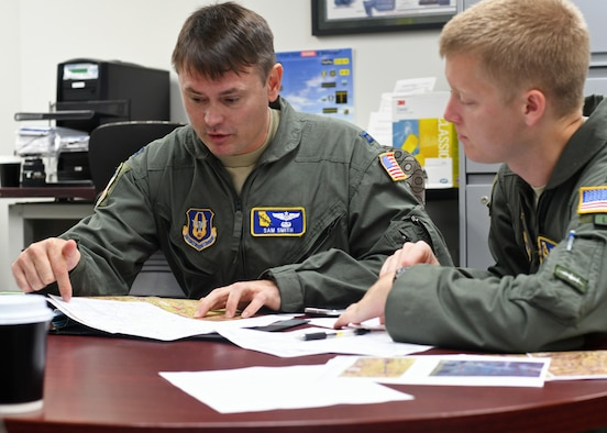 Capt. Sam Smith, 700th Airlift Squadron navigator, and 1st. Lt. Harry Downing, 700th AS pilot, conduct planning prior to a flight at Youngstown Air Reserve Station, Ohio, Aug. 7, 2018. The two, accompanied by the rest of the aircrew, were about to fly in a small formation with C-130 Hercules aircraft from both the 908th AS and the 757th AS. (U.S. Air Force photo by Staff Sgt. Miles Wilson)
