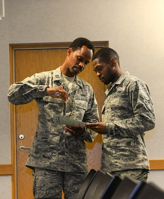 U.S Air Force Chaplain Capt. Kennie Neal, 100th Air Refueling Wing chaplain, and U.S. Air Force Airman 1st Class James Loubeau,  100th Logistics Readiness  vehicle maintenance apprentice, look over a personality test provided by the Young Airmen's Council to better understand and recognize different personalities at RAF Mildenhall, England, Aug. 22, 2018. The council has hosted several events, including panel discussions. All events are hosted, planned and by Airmen. (U.S. Air Force photo by Airman 1st Class Alexandria Lee)