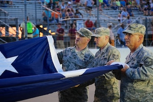 At far right, public affairs specialist and historian, Master Sgt. Gerald Sonnenberg, returned from retirement to help unfurl the American flag before the national anthem at Gateway Motorsports Park Aug. 25, 2018.  As part of the event, the 932nd Airlift Wing Maintenance Group commander, Col. Sharon Johnson, was recognized on stage with the Indy drivers at the Bommarito Automotive Group 500 race, held on a hot Saturday evening at Gateway Motorsports Park, Madison, Illinois. Johnson was an honored VIP to help kick off the IndyCar race which was won by Will Power.  He won the 248-lap race around the 1.25-mile Gateway Motorsports Park oval paved track in his #12 Chevrolet by 1.3117 seconds over second place finisher Alexander Rossi.  The 932nd Airlift Wing helped recruiting awareness and was represented by maintenance, medical, public affairs staff, retirees and operations personnel.  (U.S. Air Force photo by Lt. Col. Stan Paregien)