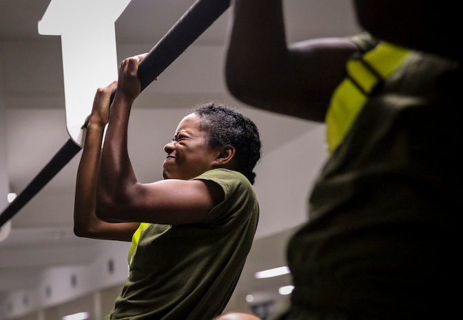 Recruits with Platoon 4038, Papa Company, 4th Recruit Training Battalion, execute pull-ups during their Initial Strength Test on Parris Island July 20, 2018. The minimum physical requirements for female recruits to begin training are 44 crunches in two minutes, 1 pull-up untimed or 15 push ups in two minutes, and a 1.5-mile run in 15 minutes.