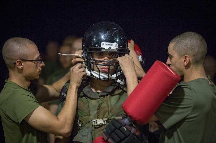 Rct. Jonathan Florentine of Platoon 2060, Echo Company, 2nd Recruit Training Battalion, has his safety gear adjusted by fellow recruits before a pugil sticks bout July 20, 2018, during the Crucible on Parris Island, S.C.
