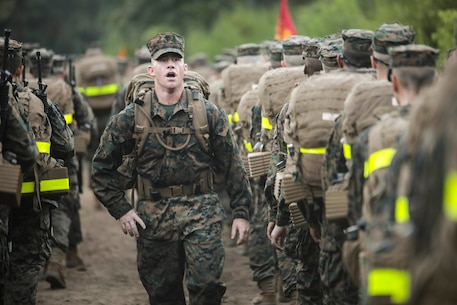A drill instructor with Mike Company, 3rd Recruit Training Battalion, motivates recruits during a 5K Hike Aug. 25, 2018 on Parris Island, S.C. The recruits, who are in their second week of recruit training, will conduct five hikes of increasing difficulty before the culminating 15K hike after the Crucible.