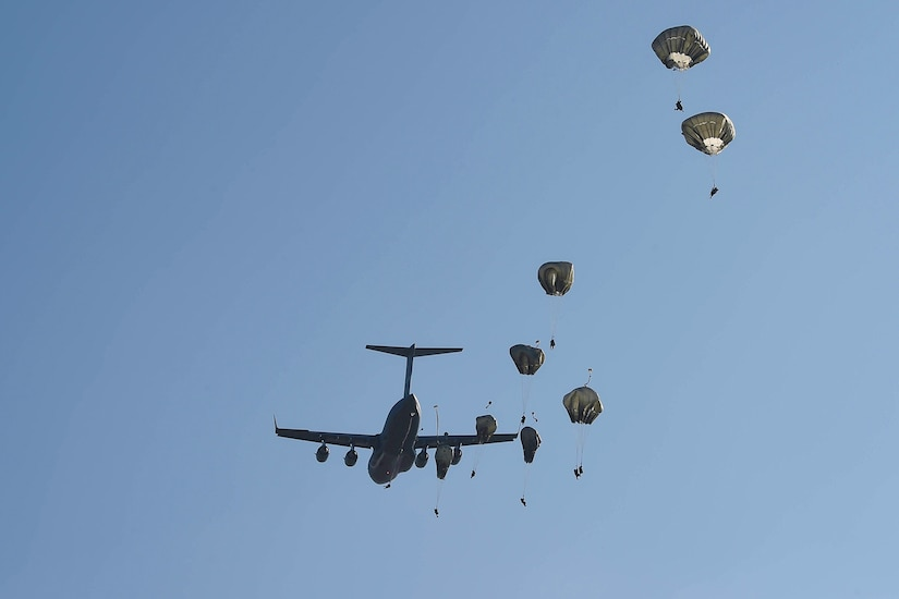 Paratroopers jump from an airplane.