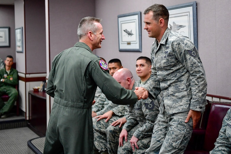 Gen. Terrence O'Shaughnessy, NORAD and USNORTHCOM commander, recognizes Staff Sgt. David Jacob, 225th Air Defense Squadron weapons director, with a commander's coin for the critical role he played during the Aug. 10, 2018 F-15 fighter intercept of the stolen Horizon Bombardier Q400 aircraft out of SeaTac International Airport.  O'Shaughnessy visited the WADS Aug. 23 in order to commend the WADS operations crew for their expert command and control of the 142nd Fighter Wing's F-15 intercept of the stolen aircraft. (U.S. Air National Guard photo by Maj. Kimberly D. Burke)