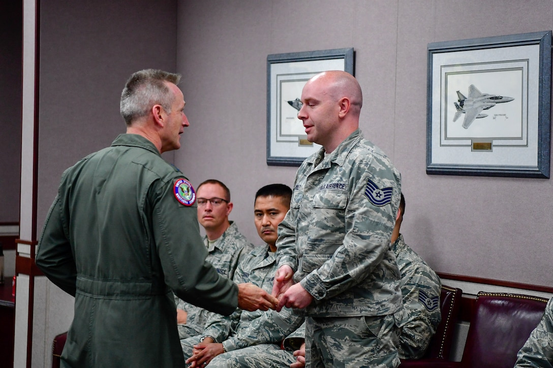 Gen. Terrence O'Shaughnessy, NORAD and USNORTHCOM commander, recognizes Tech. Sgt. Brian Kulp, 225th Air Defense Squadron weapons director, with a commander's coin for the critical role he played during the Aug. 10, 2018 F-15 fighter intercept of the stolen Horizon Bombardier Q400 aircraft out of SeaTac International Airport.  O'Shaughnessy visited the WADS Aug. 23 in order to commend the WADS operations crew for their expert command and control of the 142nd Fighter Wing's F-15 intercept of the stolen aircraft. (U.S. Air National Guard photo by Maj. Kimberly D. Burke)