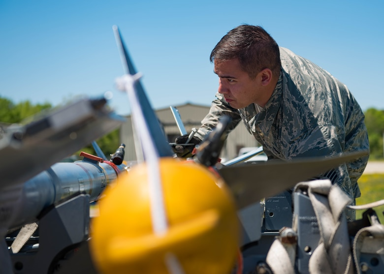 U.S. Air Force Staff Sgt. Charles Trim, 1st Maintenance Squadron precision guided munitions supervisor mounts an AIM-9 Sidewinder missile on a trailer at Joint Base Langley-Eustis, Virginia, April 30, 2018.