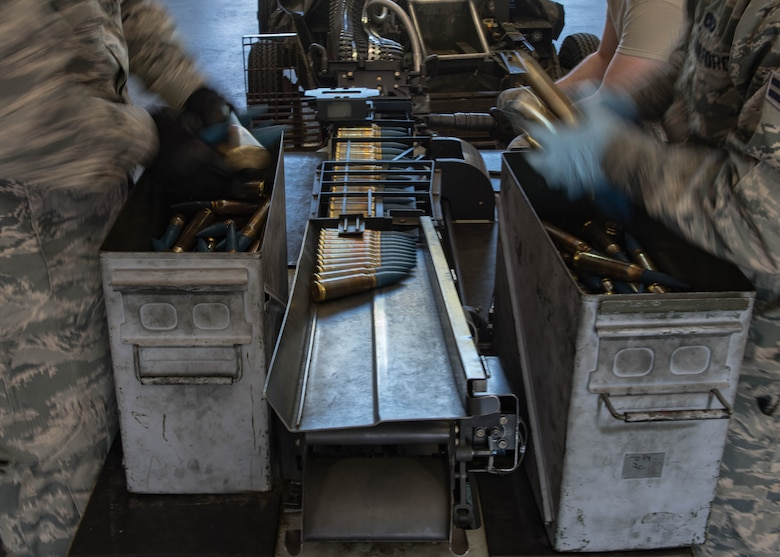 U.S. Air Force Airmen from the 1st Maintenance Squadron conventional unit, load 20 mm rounds on to a universal ammunition loading system at Joint Base Langley-Eustis, Virginia, May 1, 2018.