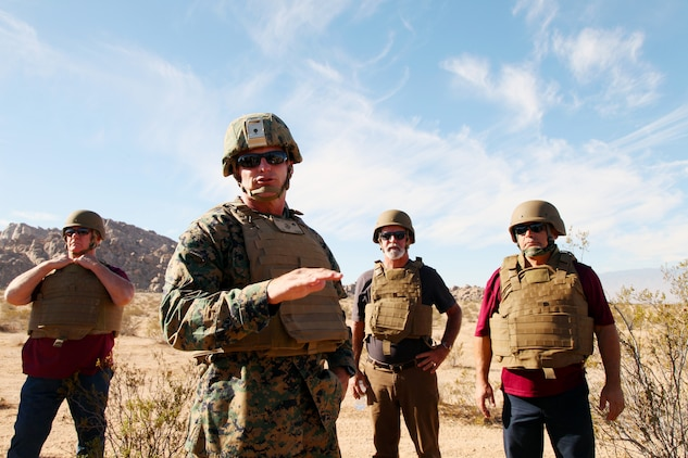 BGen Roger B. Turner Jr., Combat Center Commanding General, talks with VIP guests assembled in the Galway Lake Training Area in the Johnson Valley Exclusive Military Use Area, Marine Corps Air Ground Combat Center, Twentynine Palms, Calif., Aug. 24, 2018, before they watch members of India Company, 3rd Battalion, 4th Marines, 7th Marine Regiment, conduct live-fire training in the Exclusive Military Use Area. (Marine Corps photo by Kelly O'Sullivan)