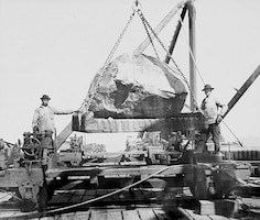 Two workers move a massive stone used in the construction of the South Jetty at the Mouth of the Columbia River in the late 1800s.
