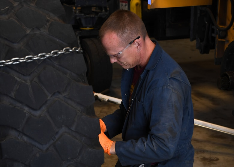 Paul Holien, 319th Logistics Readiness Squadron heavy equipment mobile mechanic, inspects a removed tire belonging to a large snow plow August 28, 2018, on Grand Forks Air Force Base, North Dakota. In addition to snow plows, the 319 LRS also maintains vehicles to include fire trucks, aerial lift trucks and additional government vehicles utilized by other squadrons around base. (U.S. Air Force photo by Airman 1st Class Elora J. Martinez)