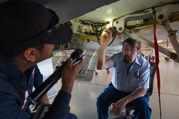 "Howard Knoll, 47th Maintenance Directorate T-38C Talon Division aircraft maintenance trainer, monitors Francisco Gallegos, 47th MXD flight attendant, inspect a T-38's landing gear. Knoll, a prior Air Force maintainer, possesses more than 30 years knowledge about the T-38, and he values passing this information on to Laughlin's maintainers and to local high schools through the ""Grow Your Own"" program to keep Laughlin pilots safe in the air. (U.S. Air Force photo by Airman 1st Class Anne McCready)"