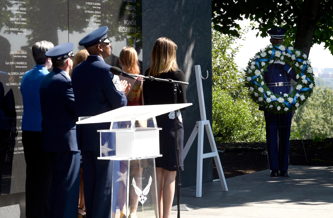 Approximately six people saluting a wreath being held by an Airman in D.C.