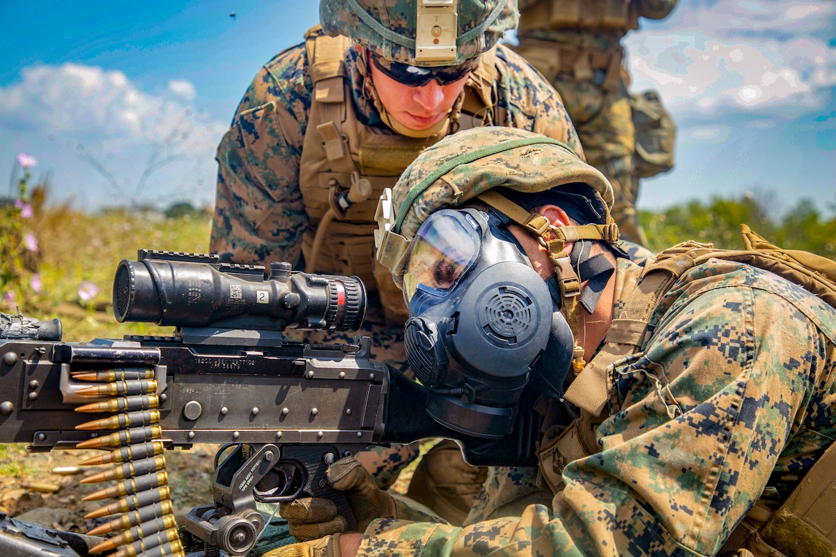 A Marine aims down his weapon while another watches closely.