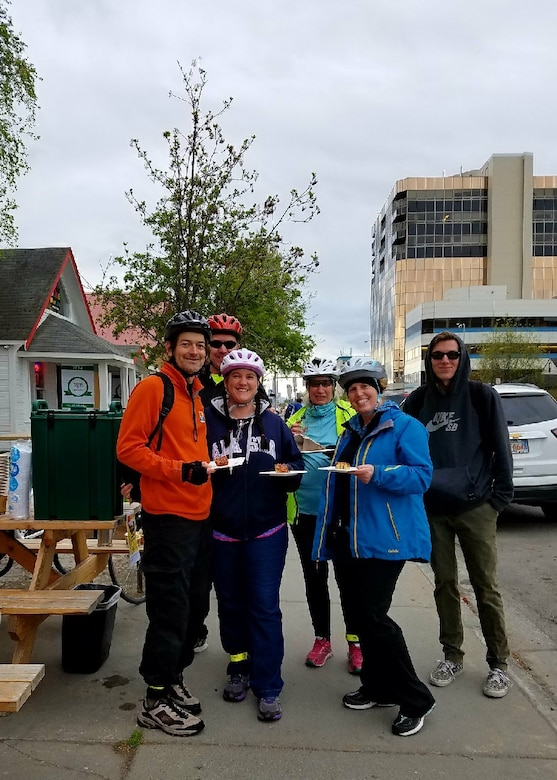 A group of Joint Base Elmendorf-Richardson 673rd Force Support Squadron cyclists receive free sticky pecan rolls from Snow City Café during their Anchorage Bike to Work Day commute in Anchorage, Alaska, May 17, 2017. En route there were designated places to take a break and receive swag and a free breakfast during the Anchorage Bike to Work Day.