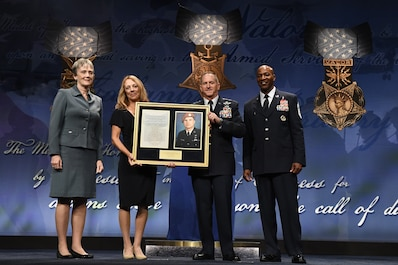 Four people standing in front of a background holding up a memorial plaque.