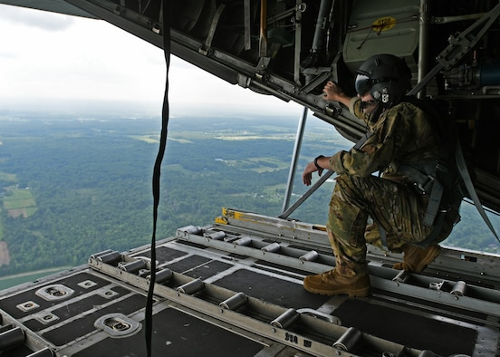 Staff Sgt. Jed Pickett, 700th Aerial Squadron loadmaster, stands on the open ramp of a C-130 Hercules as he simulates an airdrop at Youngstown Air Reserve Station, Ohio, Aug. 10, 2018. Loadmasters are responsible for physically pushing the drops out of the aircraft, as the rest of the crew navigates and directs when to drop. (U.S. Air Force photo by Staff Sgt. Miles Wilson)