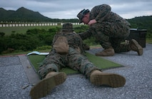 Lance Cpl. Timothy Larrigan, a range coach from Headquarters Battalion, 3rd Marine Division, gives advice to a fellow Marine during annual rifle range qualification on Camp Hansen, Okinawa, Japan, August 20, 2018. Marines qualify annually with the M16A4 service rifle to maintain combat effectiveness. Larrigan is a native of Fenton, Missouri. (U.S. Marine Corps photo by. Lance Cpl Christine Phelps)