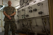 U.S. Navy Lt. Terrance Leighton, a diving medical officer with 3rd Reconnaissance Battalion, 3rd Marine Division, explains the basic operations of the compression chamber on Camp Schwab, Okinawa, Japan on June 13, 2018. The compression chamber is used to help treat service members with water pressure injures. Becoming a diving medical officer requires on average nine years of pipeline training before a candidate is ready to operate in the fleet. Leighton is a native of Boise, Idaho and an alumni of Michigan State University. (U.S. Marine Corps photo by Lance Cpl. Cameron Parks)