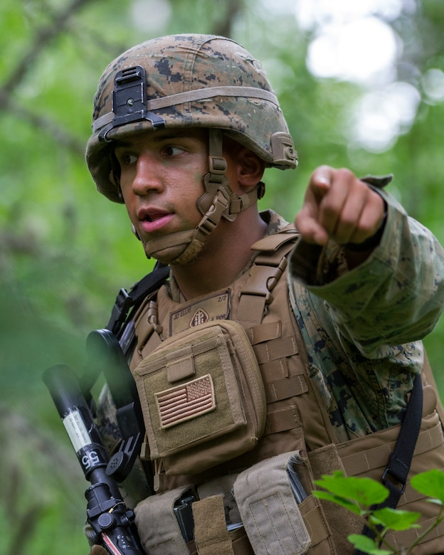 A Marine wearing combat equipment points toward the camera.