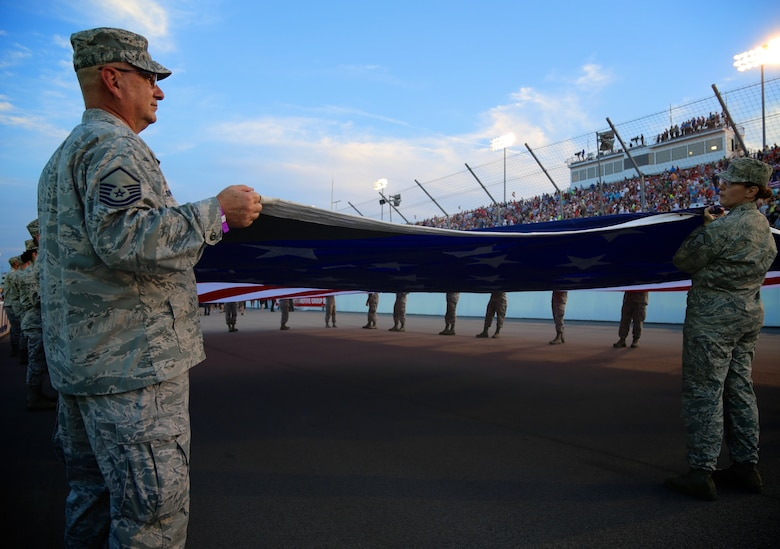 Master Sgt. Gerald Sonnenberg and Master Sgt. Karen Ridge prepare the American flag for the national anthem in front of a packed Indycar crowd August 25, 2018.  As part of the event, 932nd Airlift Wing Maintenance Group commander, Col. Sharon Johnson, was recognized on stage with the Indy drivers at the Bommarito Automotive Group 500.  The race was held at Gateway Motorsports Park, Madison, Illinois. Johnson was an honored VIP to help kick off the 2nd annual IndyCar race which was won by Will Power,  won the 248-lap race around the four-turn, 1.25-mile Gateway Motorsports Park paved track in Madison, Illinois, in his #12 Chevrolet by 1.3 seconds over second place finisher Alexander Rossi.  The 932nd Airlift Wing was represented by maintenance, medical, public affairs staff and operations personnel.  (U.S. Air Force photo by Lt. Col. Stan Paregien)