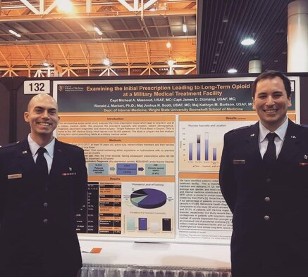 Capt. Micheal Massoud, left, and Capt. James Dizmang, standing in front of the winning poster. (Courtesy photo)