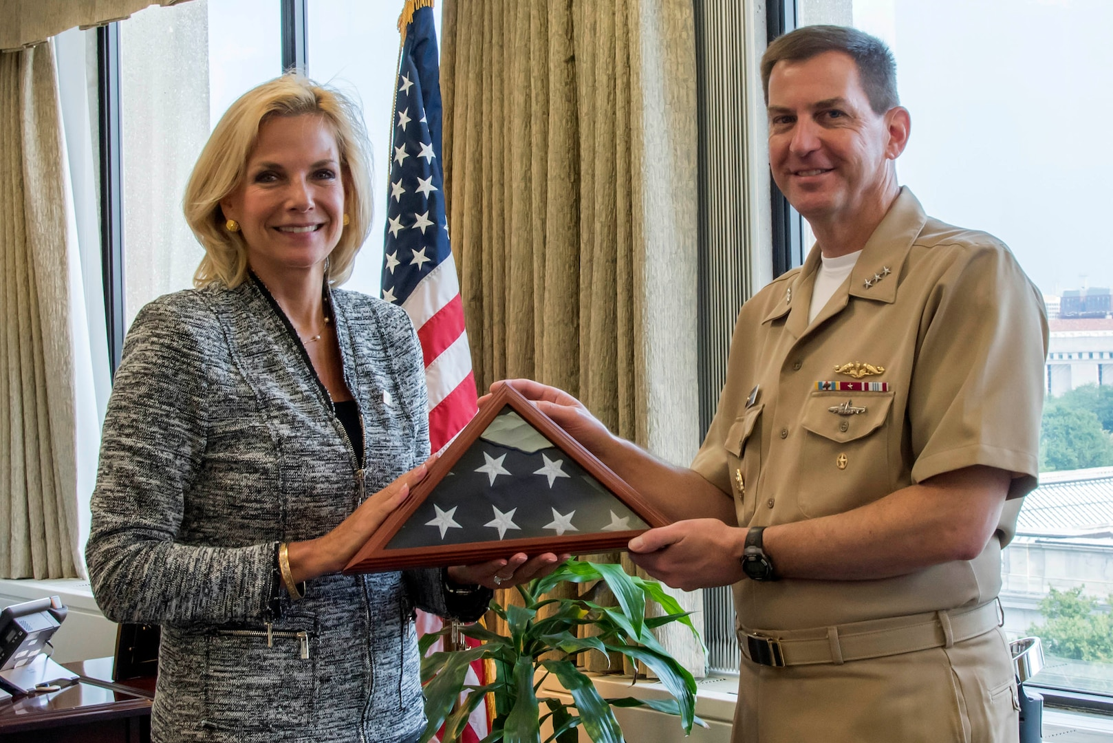 Lisa E. Gordon-Hagerty, the under secretary for Nuclear Security of the U.S. Department of Energy and administrator of the National Nuclear Security Administration (NNSA), presents U.S. Navy Vice Adm. David Kriete, the deputy commander of U.S. Strategic Command, with a U.S. flag that has been flown over every NNSA lab, plant, and site during an award ceremony at NNSA headquarters in Washington, D.C., Aug. 17, 2018.  Kriete also received the Administrator's Distinguished Service Silver award for his exceptional service as the Director of Strategic Capabilities Policy at the National Security Council from July 2016 to March 2018.