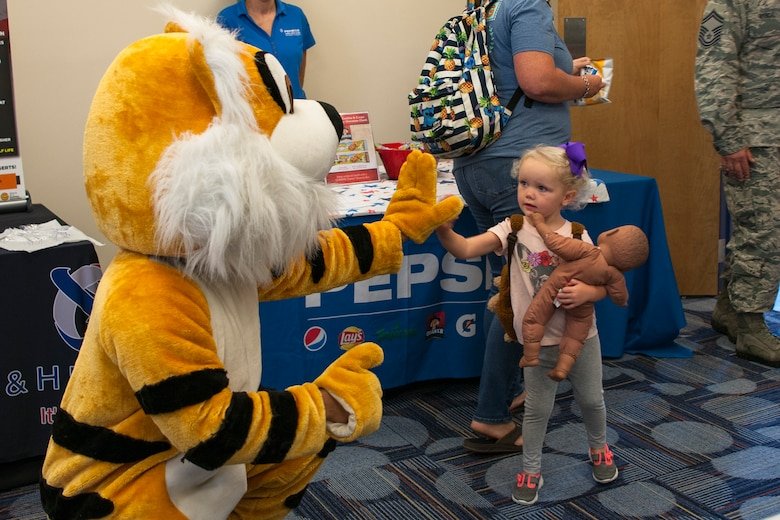 A participant high-fives the Flying Tiger during the Food Show at the Georgia Pines Dining Facility, Aug. 29, 2018, at Moody Air Force Base, Ga. The Food show is an innovative way to give Airmen an opportunity to try various healthy foods and give feedback. The event allowed the dining facility to focus on incorporating items that meet special dietary needs such as vegan, gluten-free, smoothie bar items and healthy snacks. (U.S. Air Force photo by Airman Taryn Butler)