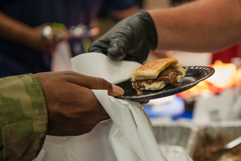 A vendor hands a sandwich to an Airman during the Food Show at the Georgia Pines Dining Facility, Aug. 29, 2018, at Moody Air Force Base, Ga. The Food show is an innovative way to give Airmen an opportunity to try various healthy foods and give feedback. The event allowed the dining facility to focus on incorporating items that meet special dietary needs such as vegan, gluten-free, smoothie bar items and healthy snacks. (U.S. Air Force photo by Airman Taryn Butler)