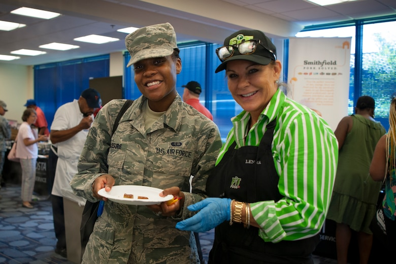 Senior Airman Shania Desaussure, left, 23d Force Support Squadron food service journeyman, and a vendor pose for a photo during the Food Show at the Georgia Pines Dining Facility, Aug. 29, 2018, at Moody Air Force Base, Ga. The Food show is an innovative way to give Airmen an opportunity to try various healthy foods and give feedback. The event allowed the dining facility to focus on incorporating items that meet special dietary needs such as vegan, gluten-free, smoothie bar items and healthy snacks. (U.S. Air Force photo by Airman Taryn Butler)