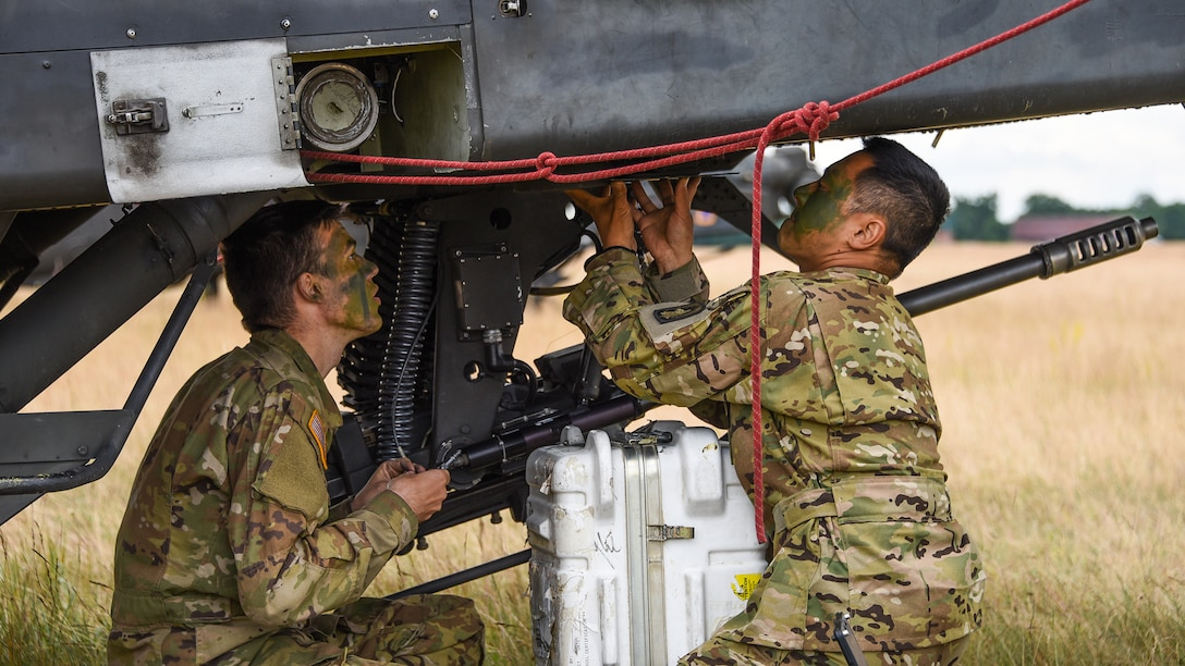 Army Sgt. Nathan Choi and Pfc. Matthew Hanneman from the 12th Combat Aviation Brigade conduct maintenance on AH-64 Apache helicopter during Saber Strike 2018 at Bemowo Piskie Training Area in Orzysz, Poland. DLA equipped exercise participants with everything from repair parts to fuel.