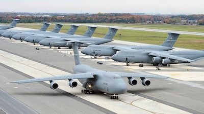 A C-5 Galaxy taxis past a line of C-5s sitting on the tarmac at Travis Air Force Base, California. DLA Aviation manages more than 74,000 parts for the C-5, which the Air Force is planning to keep in its arsenal until at least 2040.