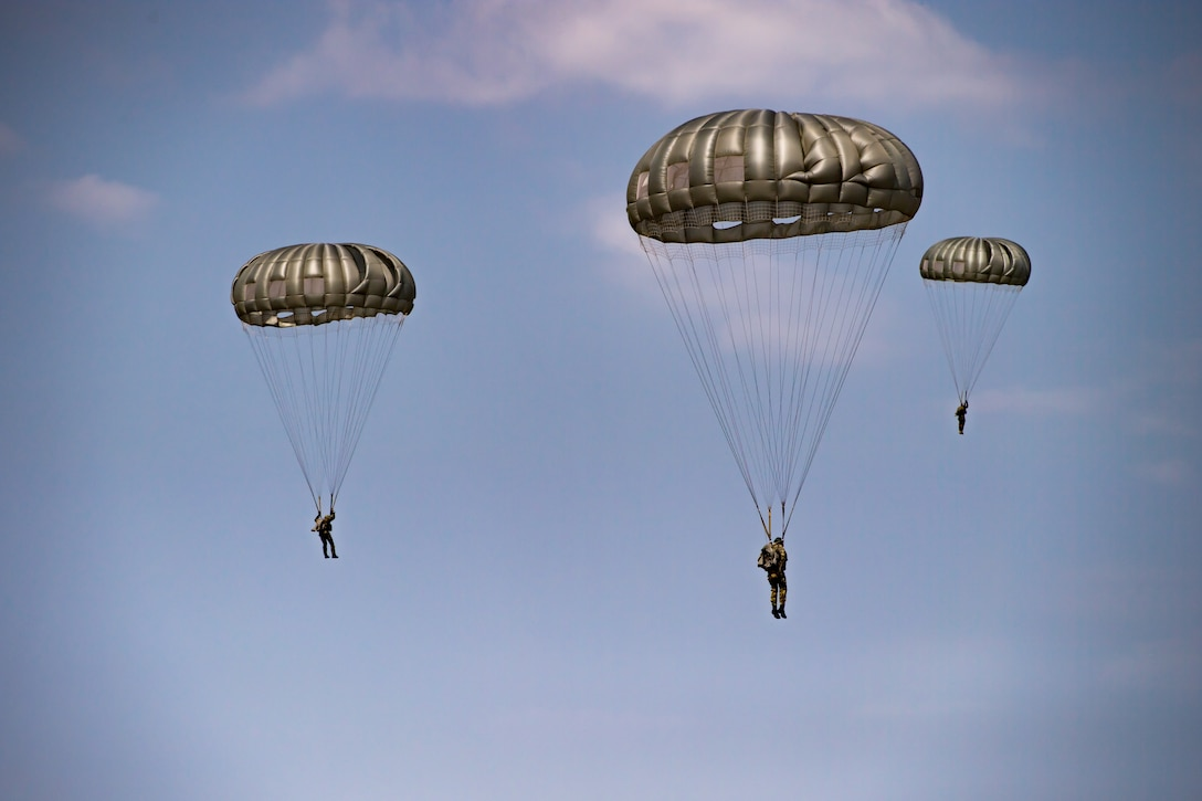 Romanian air force paratroopers descend from the sky after jumping out of a U.S. Air Force C-130J Super Hercules aircraft assigned to the 37th Airlift Squadron, Ramstein Air Base, Germany, over Boboc Air Base, Romania, Aug. 23, 2018. The airdrops were part of exercise Carpathian Summer 2018, a bilateral training exercise designed to enhance interoperability and readiness of forces by conducting combined air operations with the Romanian air force. (U.S. Air Force photo by Senior Airman Devin Boyer)