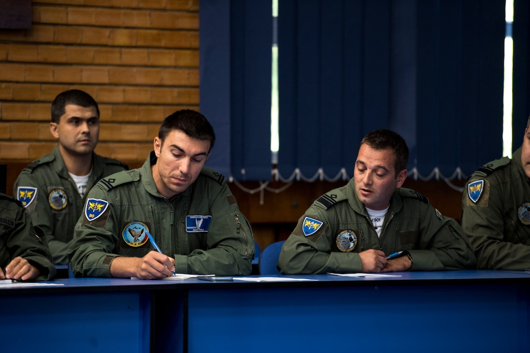Romanian air force personnel take notes during a brief for exercise Carpathian Summer 2018 on Otopeni Air Base, Romania, Aug. 22, 2018. During the brief, U.S. Air Force and Romanian air force personnel discussed objectives for the exercise. (U.S. Air Force photo by Senior Airman Devin Boyer)
