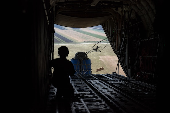U.S. Air Force Staff Sgt. Sarah Meadows, 37th Airlift Squadron loadmaster releases a container delivery system with her wingmen during an airdrop over Boboc Air Base, Romania, Aug. 27, 2018. The CDS is a commonly used method for the aerial insertion of supplies for contingency operations. (U.S. Air Force photo by Senior Airman Devin Boyer)