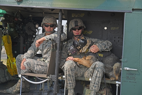 Staff Sgt. Daniel Tabita and Staff Sgt. Kyle Wentz, 92nd Security Forces Squadron Military Working Dog handlers, and MWD Brenda prepare to fly during huey training with the 36th Rescue Squadron Aug. 15, 2018, at Fairchild Air Force Base, Washington. For nearly every dog, it was their first time all four paws have left the ground. For a MWD team, being prepared before heading downrange is imperative to ensuring they meet deployment objectives. (U.S. Air Force photo/Staff Sgt. Mackenzie Mendez)