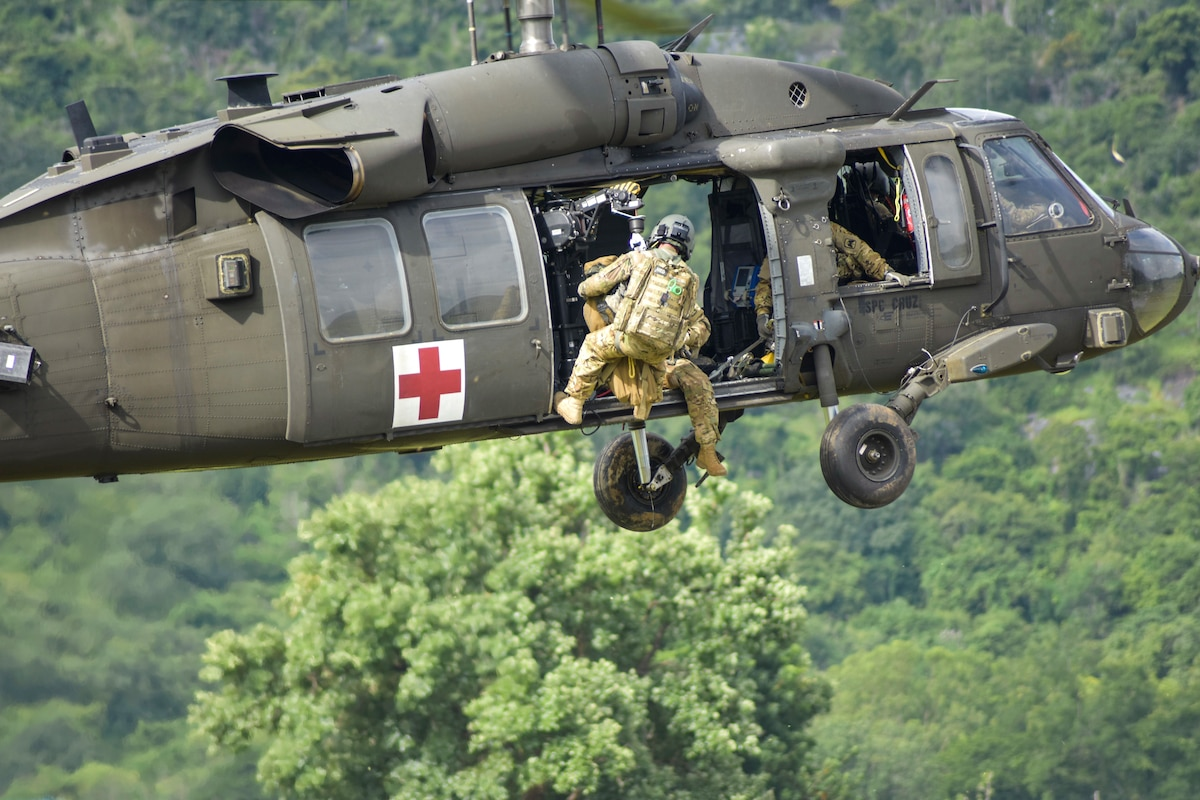 A soldier hangs out the open door of a hovering helicopter.
