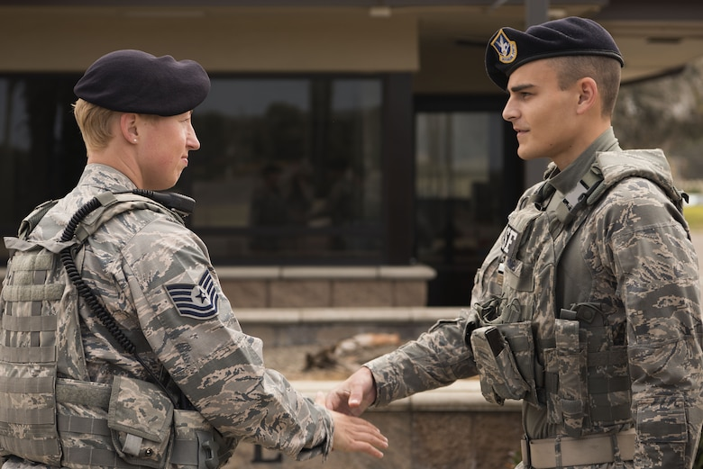 Tech. Sgt. April Spilde, flight chief for the 30th Security Forces Squadron, shakes hands with Airman 1st Class Marcus Hammel, Charlie flight member, during a post check August 2, 2018, on Vandenberg Air Force base. Spilde manages one flight of Airmen and makes sure they are able to perform their daily duties. (U.S. Air Force photo by Airman 1st Class Hanah Abercrombie)