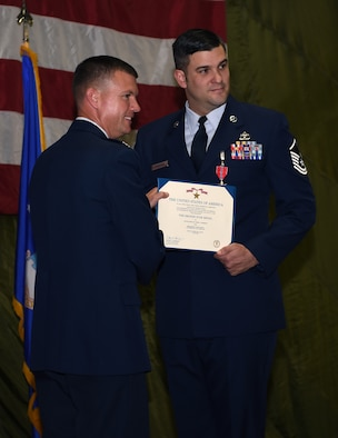 Col. Scovill W. Currin, 62nd Airlift Wing Commander, presents the Bronze Star award to Master Sgt. Derek J. Thompson, inside the 62nd Aerial Port Squadron August 28, 2018.