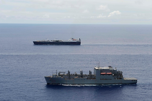 Military Sealift Command ships, vehicle cargo ship USNS Dahl and the dry cargo ship USNS Lewis and Clark, sail in formation in the Pacific Ocean.