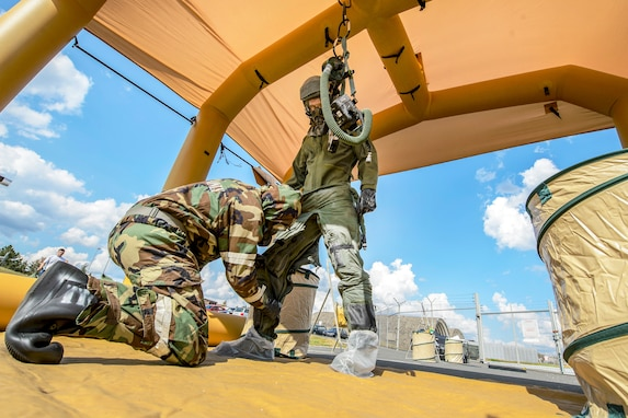 Senior Airman Austin Lebrun, left, 52nd Operation Support Squadron aircrew flight equipment journeyman, works on decontaminating Capt. Logan Mitchell, 52nd OSS AFE flight commander, during decontamination training at Spangdahlem Air Base, Germany, Aug. 23, 2018. The training involved a nine-station decontamination process demonstrating that the mission can still be accomplished in a chemical, biological, radiological and nuclear environment. (U.S. Air Force photo by Staff Sgt. Jonathan Snyder)