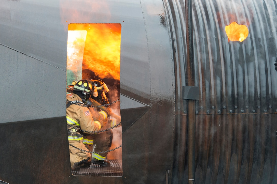 Fire protection specialists assigned to the 673rd Civil Engineer Squadron battle a simulated aircraft fire during wartime-firefighting readiness training at Joint Base Elmendorf-Richardson, Alaska, Aug. 23, 2018. During the readiness training the firefighters donned various levels of mission oriented protective posture gear and practiced responding to emergency situations in a simulated toxic environment during a chemical, biological, radiological or nuclear strike. (U.S. Air Force photo by Alejandro Peña)