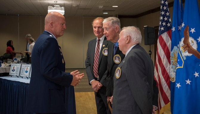 """Gen. Jay Raymond, Commander of Air Force Space Command and Joint Force Space Component Commander, Mr. William N. Barker, retired Brig. Gen. Joseph D. Mirth and retired Col. Robert W. """"Rob"""" Roy converse after the Air Force Space and Missile Pioneers Hall of Fame induction ceremony at Peterson Air Force Base, Colorado, Aug. 28. (US Air Force photo/Dave Grim)"""