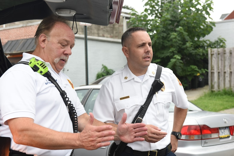 Scott Little, right, fire chief of Lancaster's Bureau of Fire, gets briefed on the scene of a gas leak by the on-scene battalion chief Aug. 21, 2018, Lancaster, Pennsylvania. A pipe was struck during road work that created a gas leak, which resulted the road being closed off for hours until it was under control. (U.S. Air National Guard photo by Senior Airman Julia Sorber/Released)
