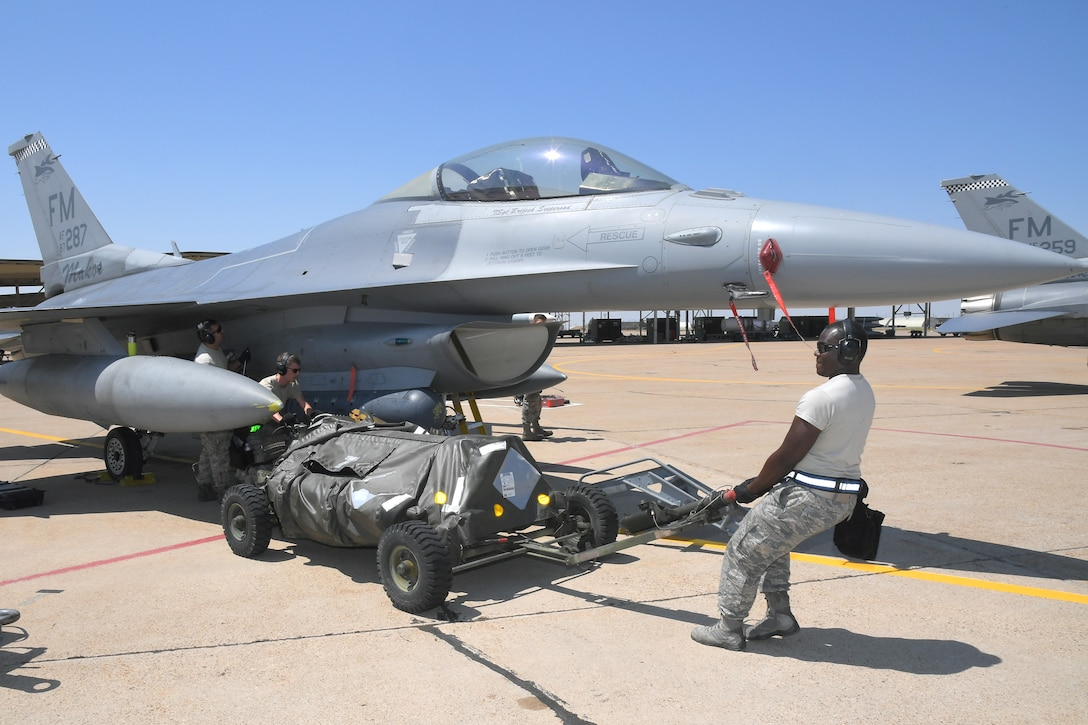 (Left to right) Senior Airman Jeremy Watson and Tech. Sgt. Darian Willis, 482nd Aircraft Maintenance Squadron, reposition an ammo cart for loading target rounds on an F-16, Aug. 8, 2018, at Hill Air Force Base, Utah. The 482nd AMXS from Homestead Air Reserve Base, Fla., was at Hill AFB to participate in the Air Force's Weapon System Evaluation Program known as Combat Hammer. (U.S. Air Force photo by Todd Cromar)
