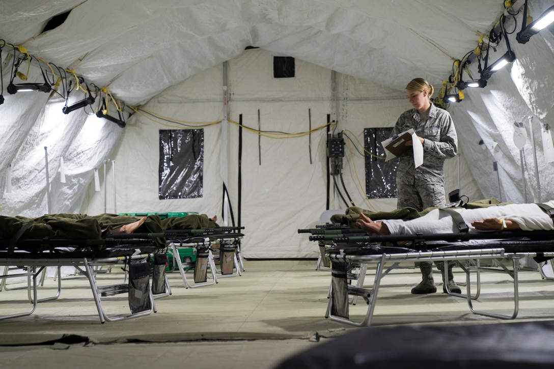 U.S. Air Force Reserve 1st Lt. Rebekah Howe, 60th Medical Group clinical nurse, reviews patient information inside an Air Force Expeditionary Medical Support System tent during Exercise Ultimate Caduceus 2018 at Travis Air Force Base, California, Aug. 22, 2018. Ultimate Caduceus 2018 is an annual patient movement exercise designed to test the ability of U.S. Transportation Command to provide medical evacuation. (U.S. Air Force photo by Jamal D. Sutter)