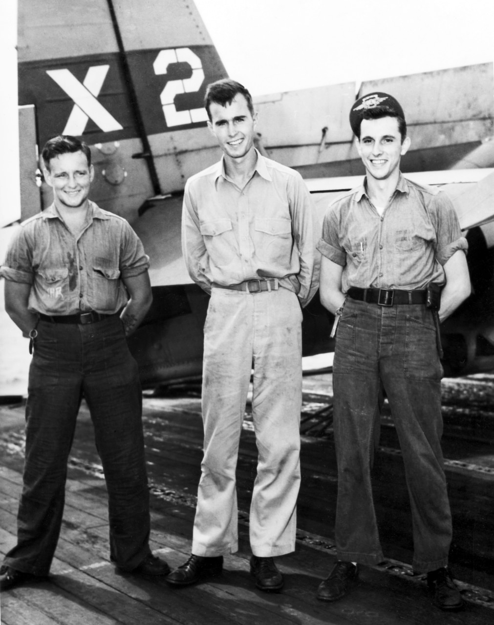 Three WWII-era naval aviators stand in front of their aircraft.