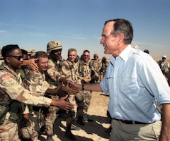 President George H.W. Bush shakes hands with U.S. troops.