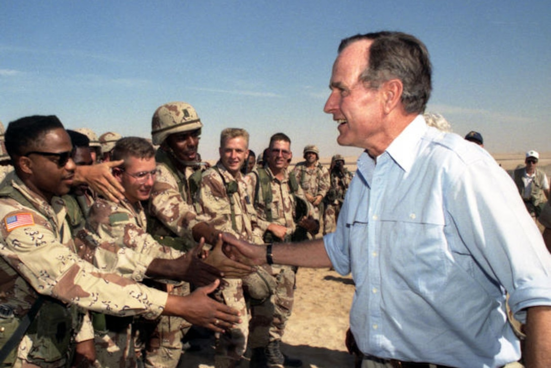 President George H.W. Bush shakes hands with troops.